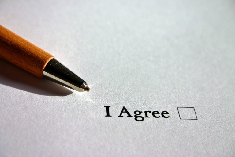 """A pen rests just above an unfilled check box that says """"I agree""""."""