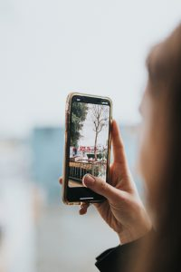 Woman takes a photograph of a tree on her smartphone