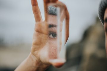 A woman holds up a piece of glass. Her eye is visible in the reflection.